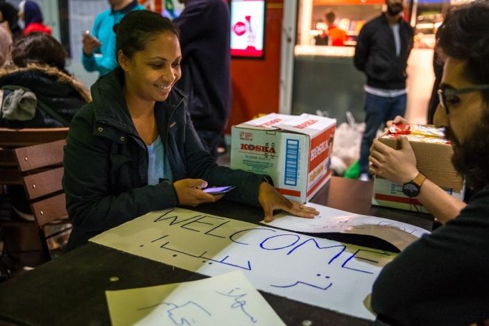 Freiwillige empfangen ankommende Flüchtlinge